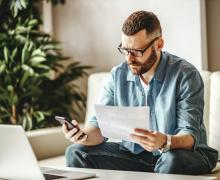 Man looking at phone and laptop
